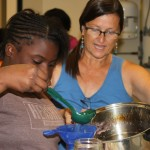 Volunteer helping 4-H'er learn how to make jelly