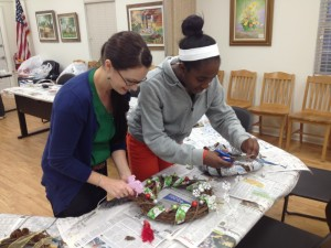 Gulf County adult 4-H Club leader assists a 4-Her on the finishing  touches of her grapevine wreath.