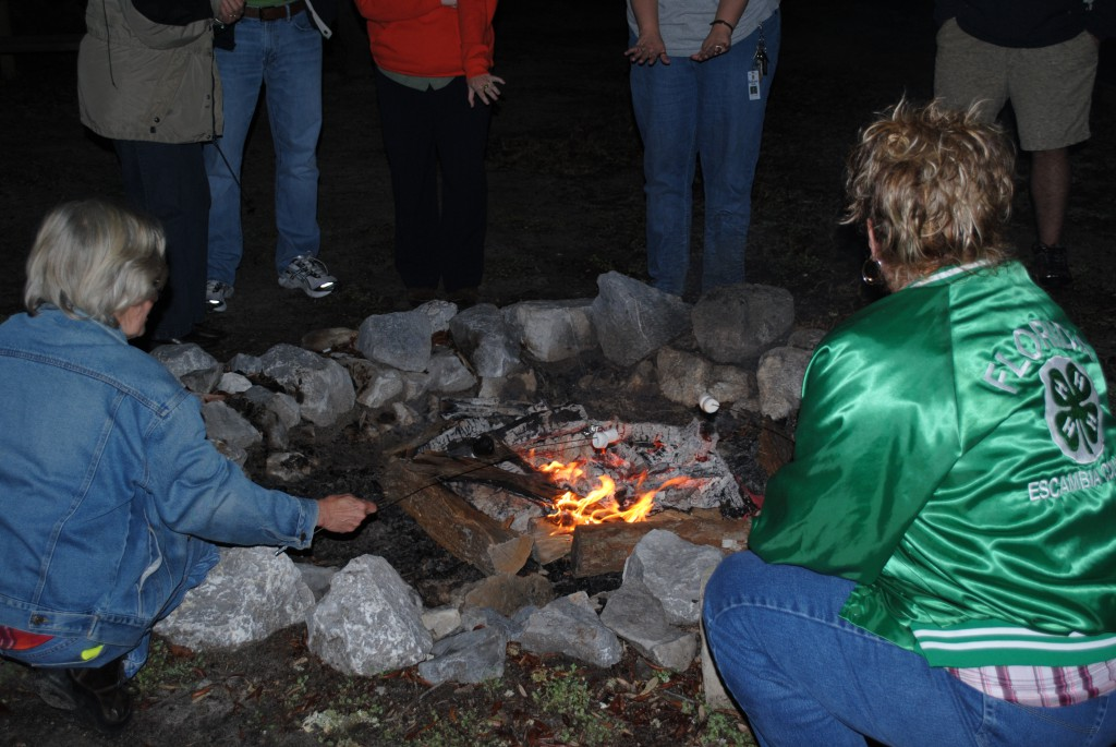 4-H Volunteers cook s'mores over the campfire at Camp Timpoochee
