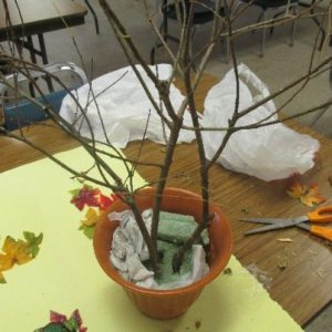 Use tissue paper or florists' foam to secure the branched in your decorative container.