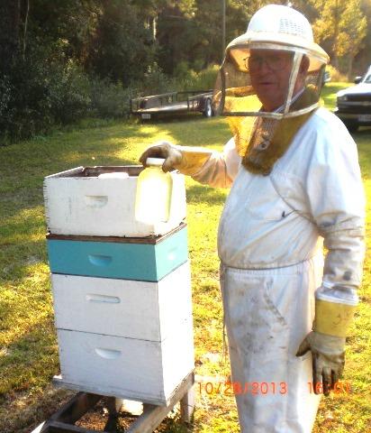 Gulf County Beekeeper, Eddie Causey feeding honeybees corn syrup.  Photo credit:  Roy Carter