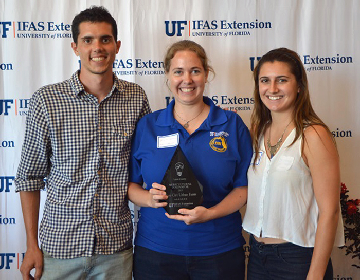 David Newman (left), Hanah Newman (right) and Tyler Murphey (not pictured) were honored as Agricultural Innovators in Leon County by Molly Jameson, Leon COunty Extension (center).