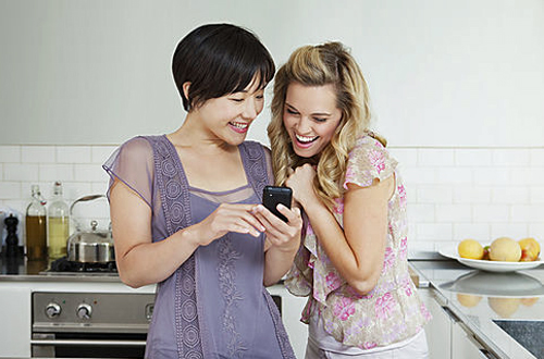 Laughing women using cell phone