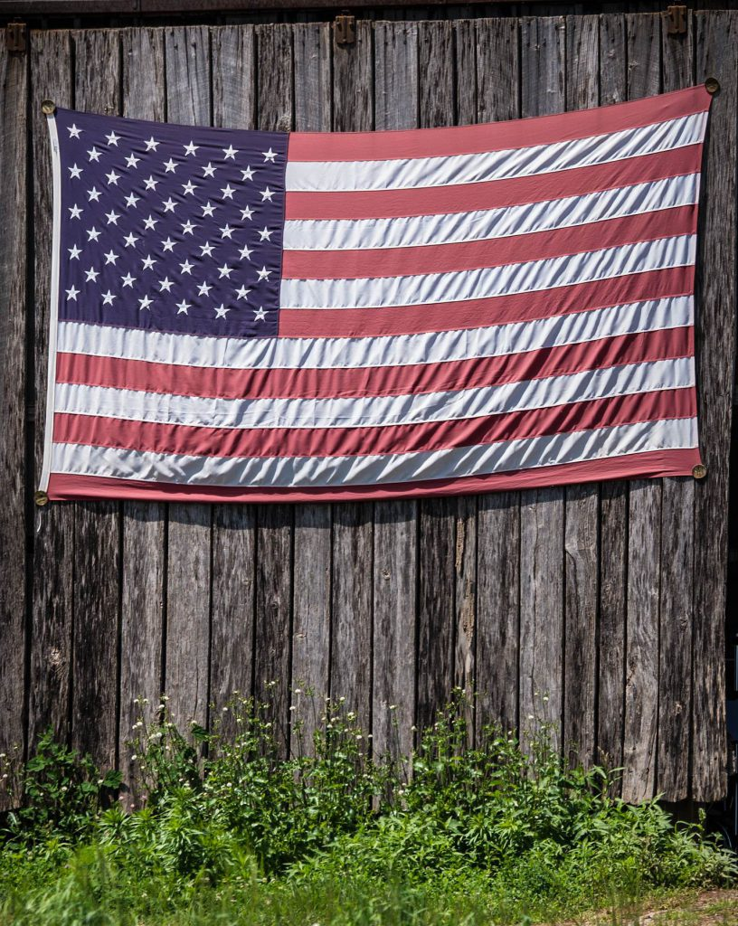 The American flag is displayed on Bigg Riggs farm owned by U.S. Marine Corps (USMC) veteran Calvin Riggleman in Hampshire County, WV on Wednesday, Jun. 24, 2015. Riggleman served in Iraq and serves his community farm fresh organic produce, and food products made by the Bigg Riggs Farm team. For the rest of veteran Calvin Riggleman's story, please see the addendum to this article below. USDA Photo by Lance Cheung. 20150624-FFAS-LSC-0095 USDA Photostream